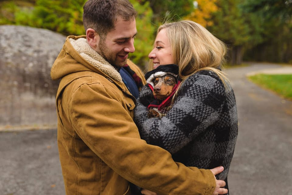 Couple hugging dog in their coats