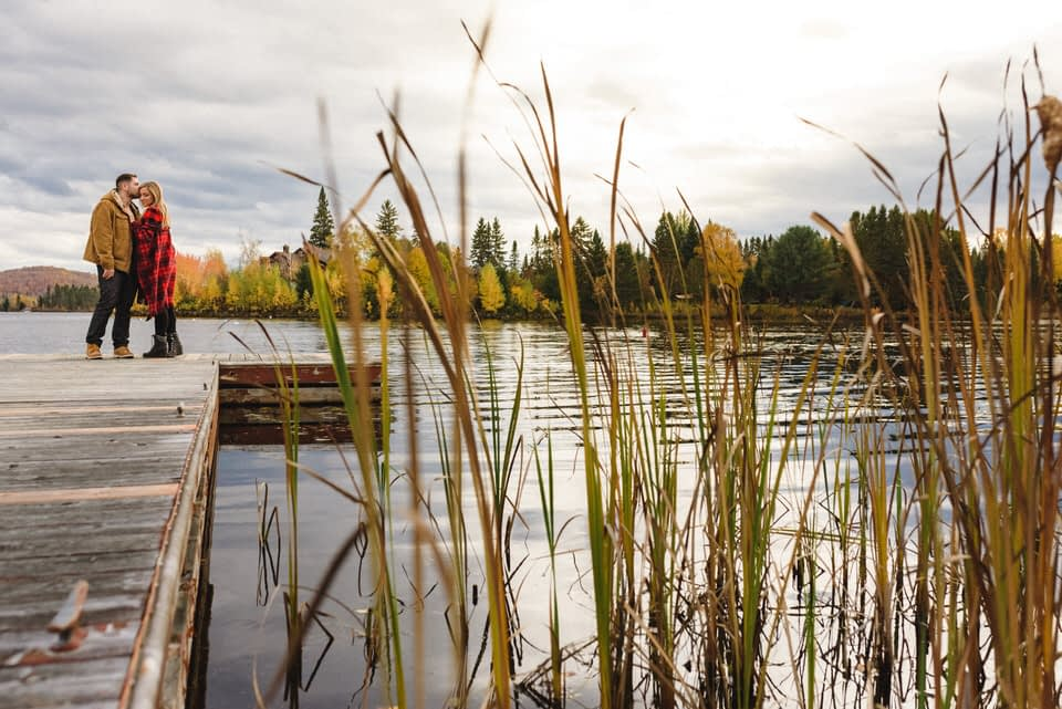 Couple kissing on dock in the fall, framed by tall grasses
