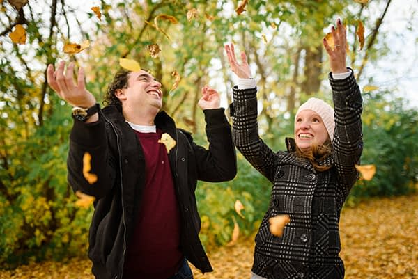 Engaged couple throwing leaves in the air