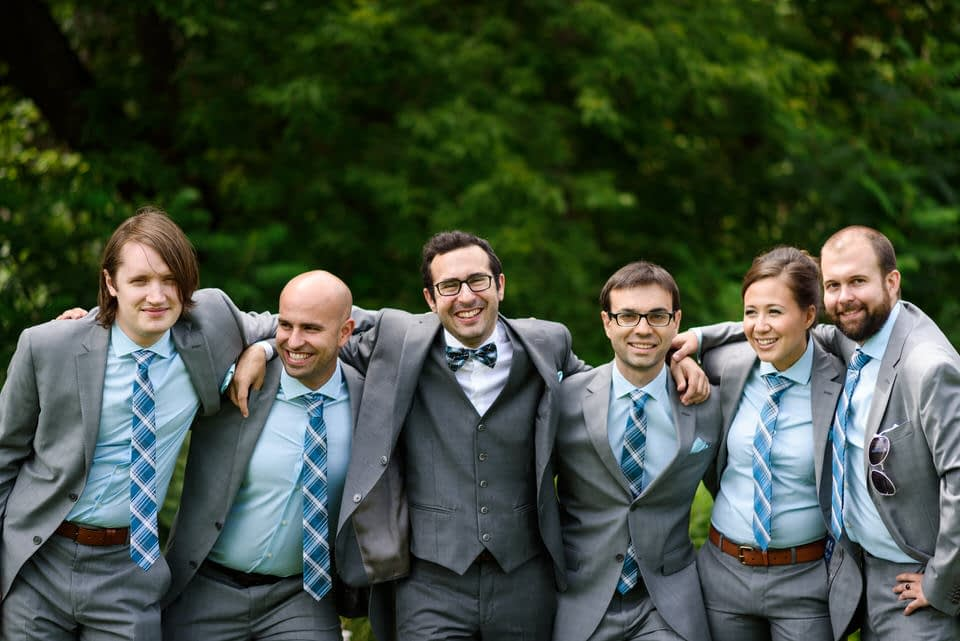 Groom with arms around friends
