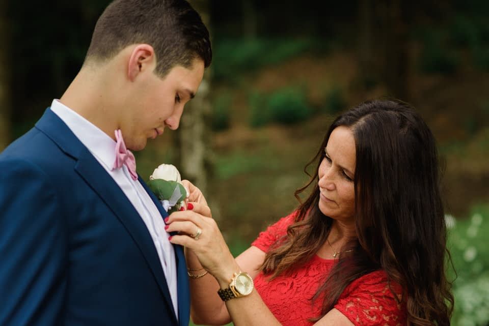 Groom's mom helping him pin on boutonniere