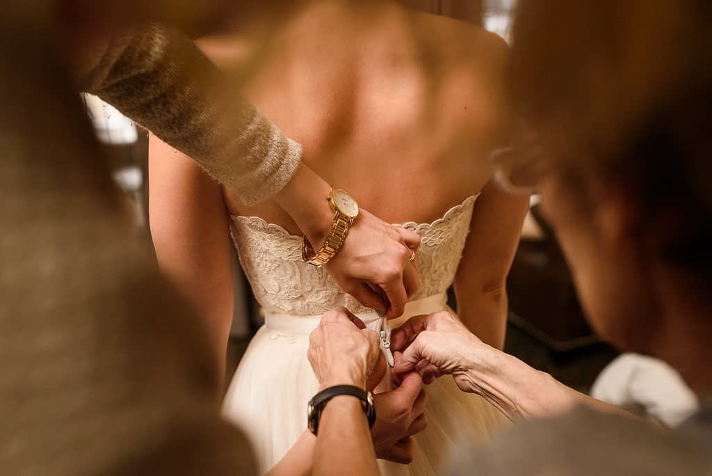 Four hands buttoning up the bride's wedding dress