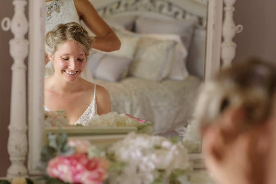 Bride laughing in mirror as she gets her hair done