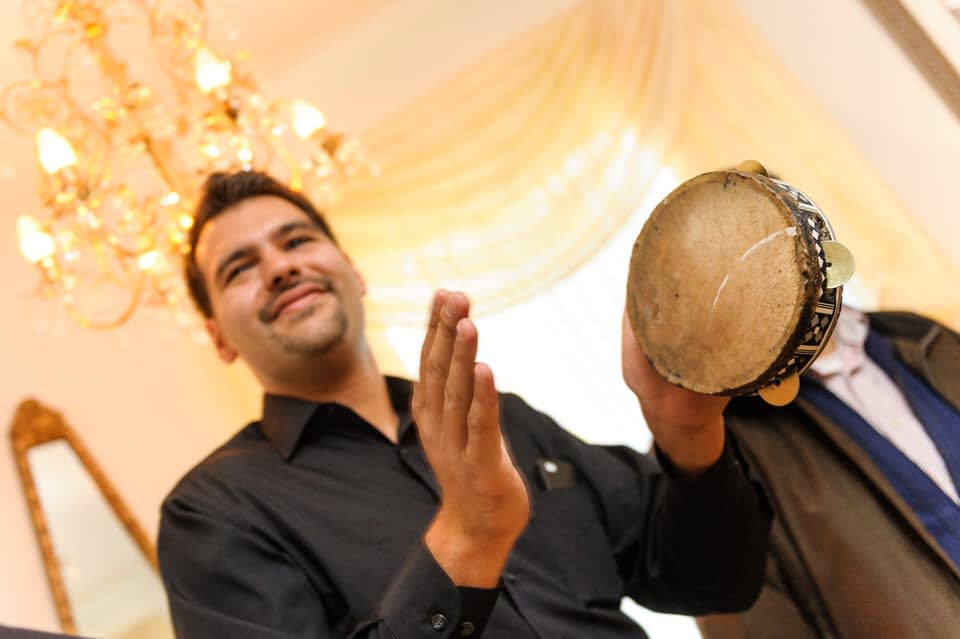 Man playing a small drum to celebrate the bride's arrival