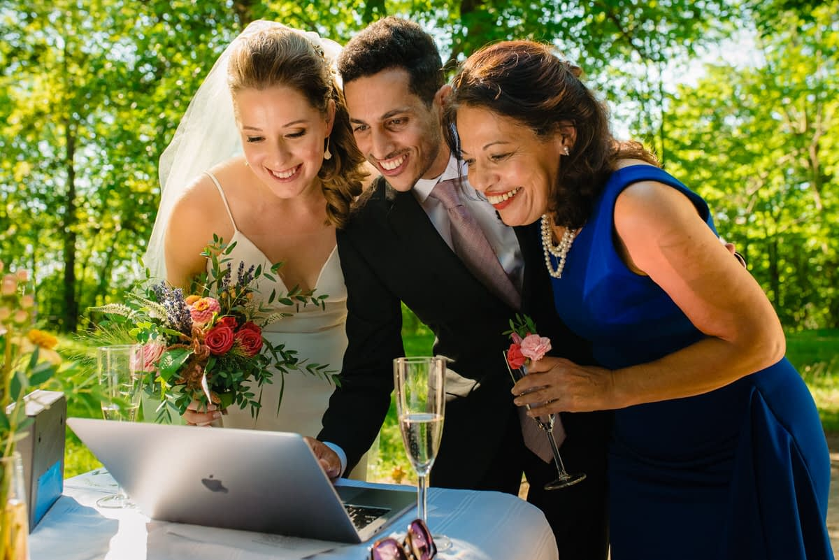 Bride, groom and his mom video chat with family during COVID wedding in a park