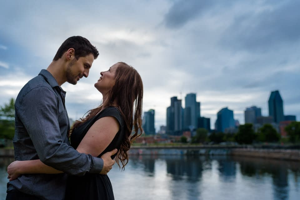 Engagement portrait along Lachine Canal with Montreal skyline behind them