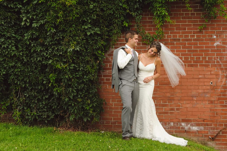 Bride and groom laughing as her veil blows in the wind