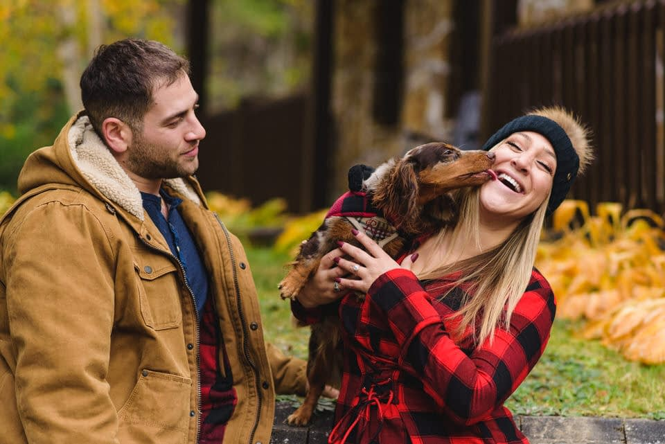 Engagement photo with dog licking woman's face as her fiancé looks on