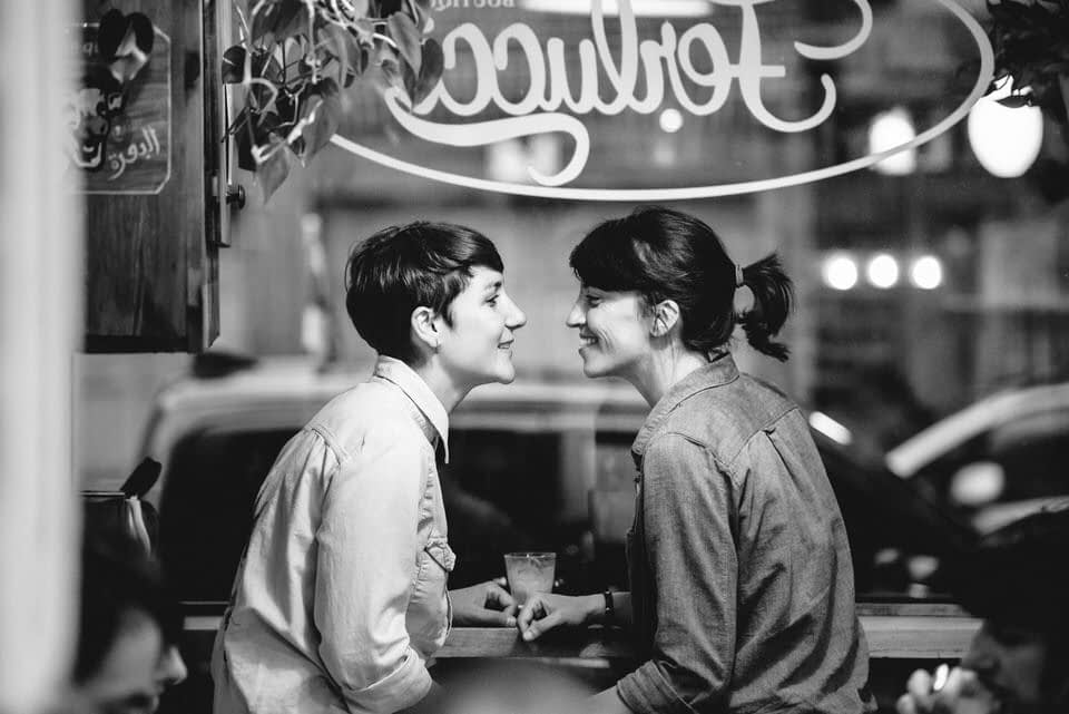 Engaged lesbian couple in romantic photo at Montreal cafe
