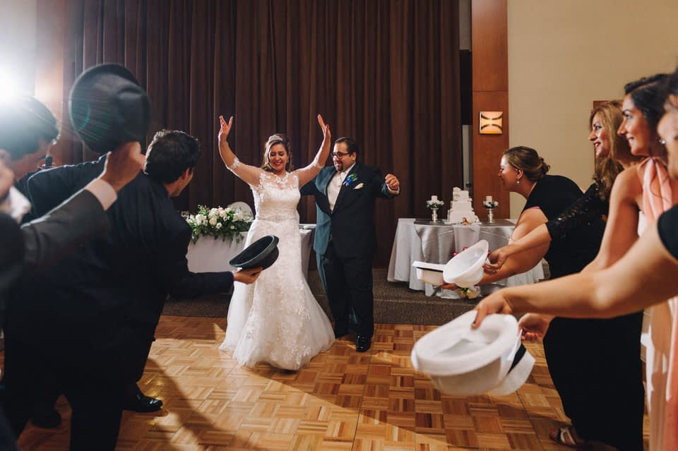 Guests dancing around bride and groom with hats