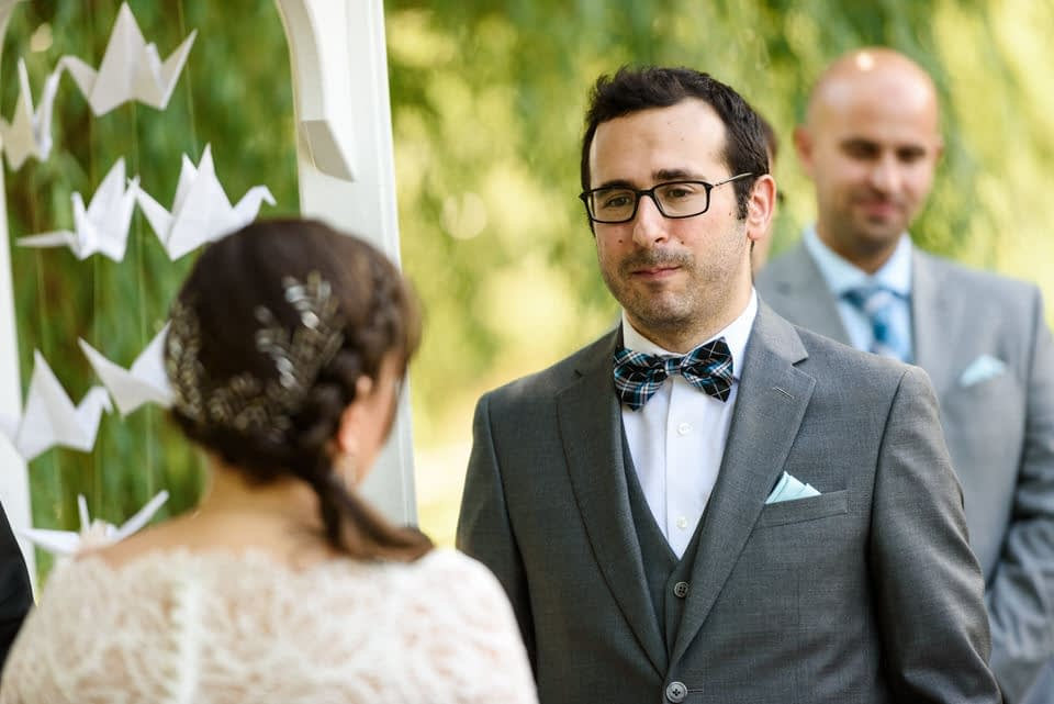 Groom listening to vows at outdoor wedding ceremony