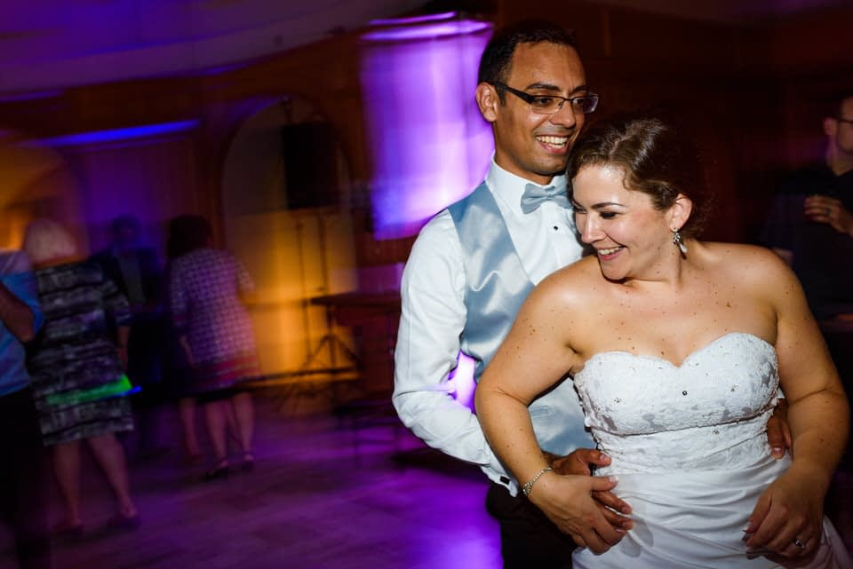 Bride and groom dancing together at night