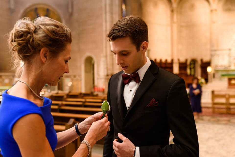 Groom's mother pinning boutonnière on groom
