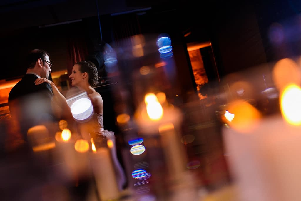 Bride and groom dancing surrounded by glow of candles