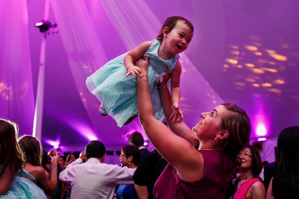 Wedding guest lifting daughter in the air
