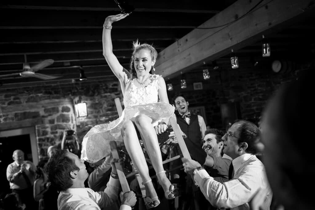 Bride being lifted up on chair