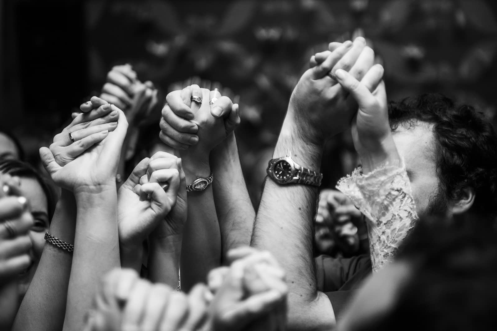 Hands in the air as wedding guests dance together