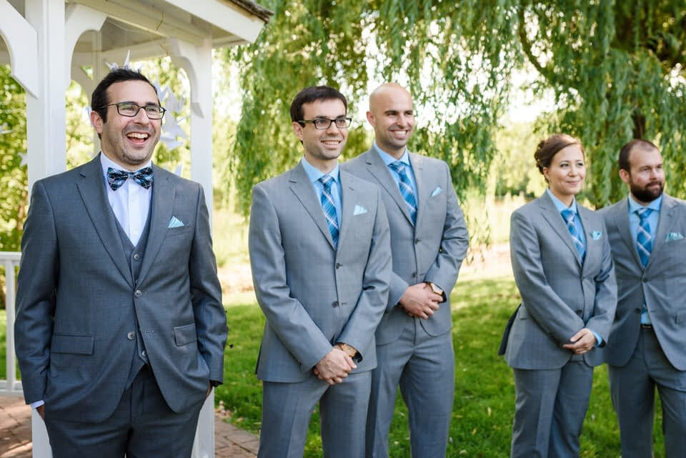 Groom waiting with friends at ceremony