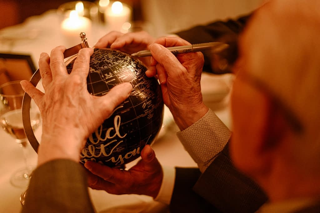 Wedding guest signing the globe guestbook