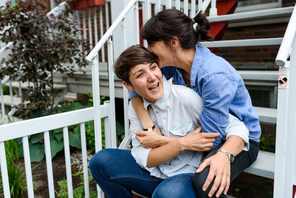 Lesbian couple laughing and hugging on stairs