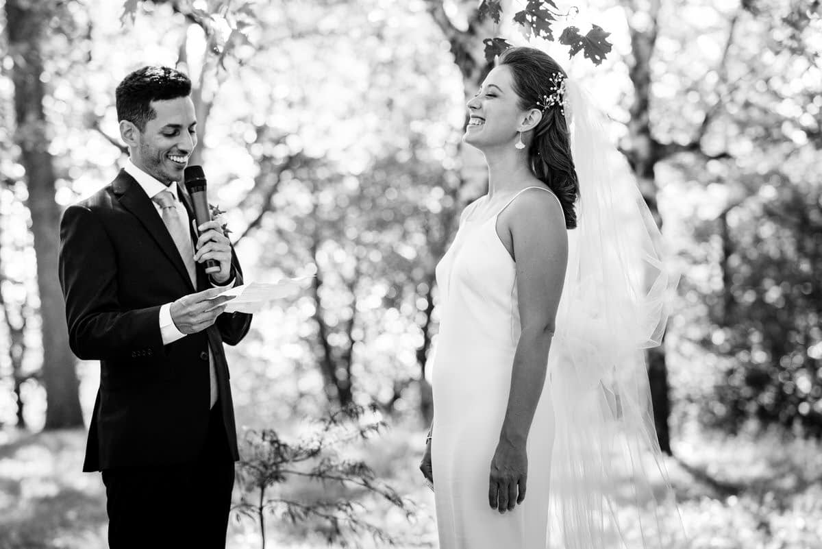 Bride laughing during the groom's wedding vows