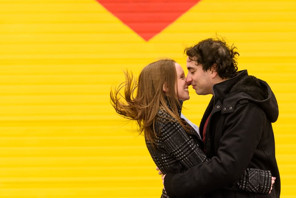 Newly engaged kissing in the wind in front of graffiti mural in Montreal