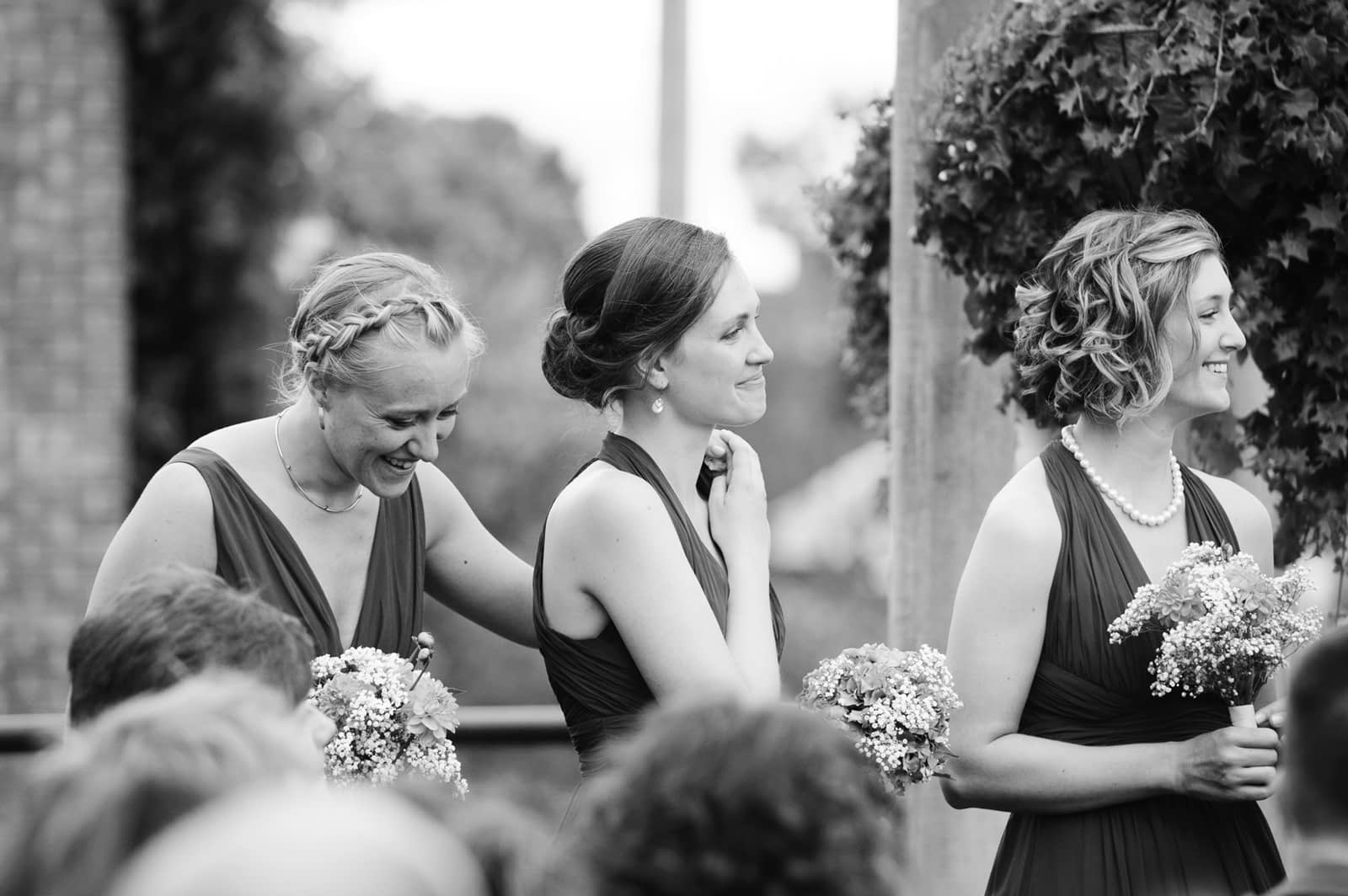 Bridesmaids holding hands and laughing at the ceremony