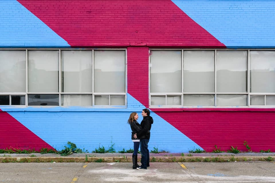 Couple holding each other in front of graffiti mural in Montreal