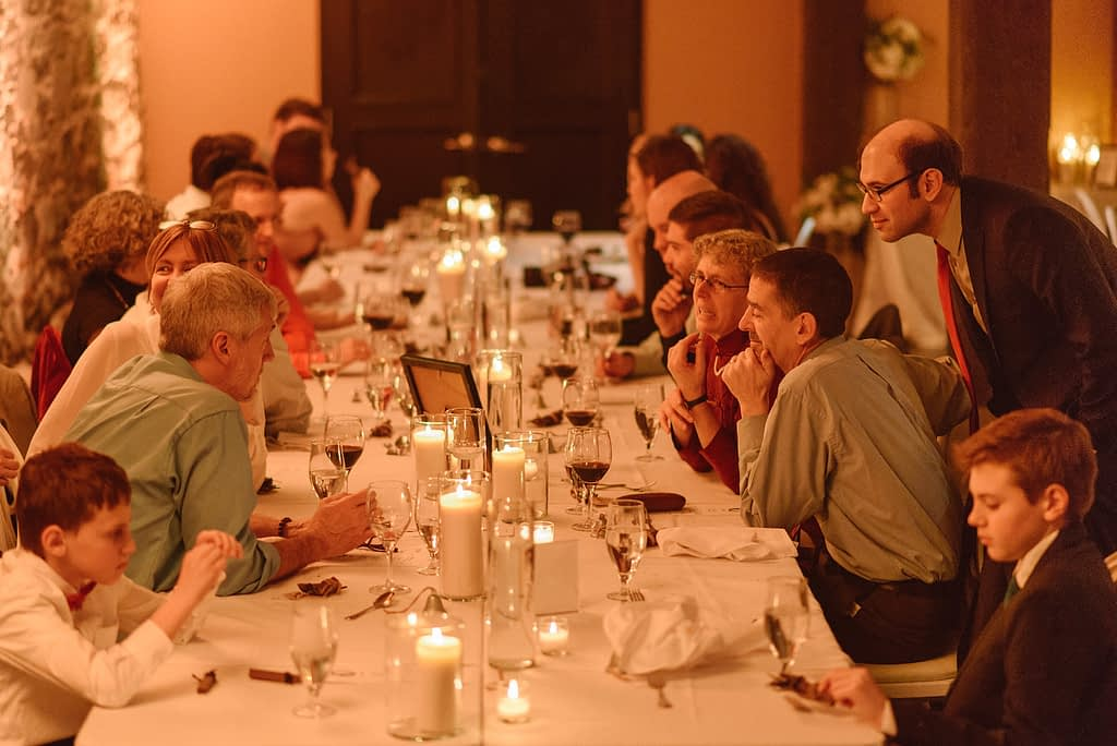 View of wedding table by candlelight with guests chatting