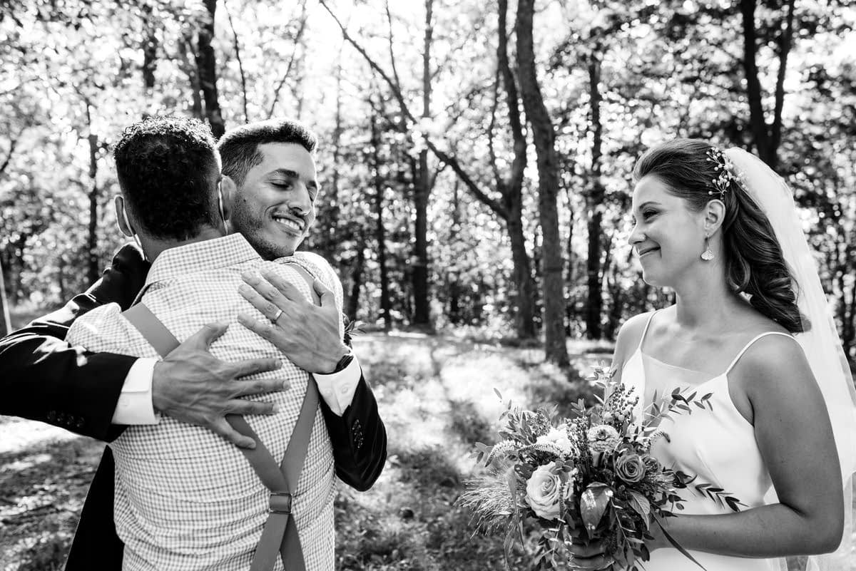 Groom receives a hug from family member as bride looks on