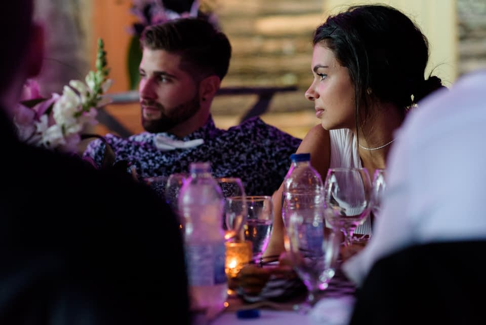 Wedding guests at dinner with candlelight under tent
